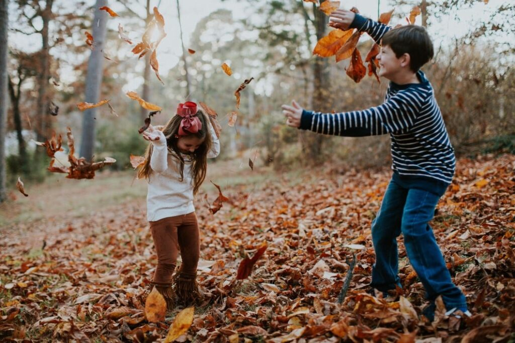 young kids having leaf fight